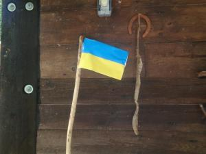 Still life with walking stick, Ukrainian flag, horseshoe, snakeskin, light switch and refurbished pillar