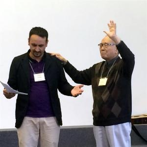 Pastor Wang prays for Ionel Cocos, Roma leader from Romania